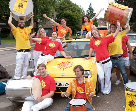 Sol Samba drummers posing in front of the samba mobile